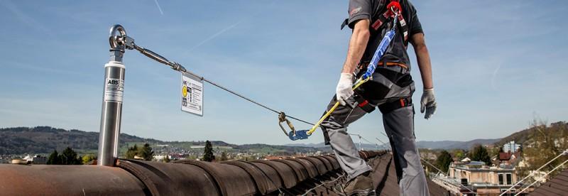 Arbeiter auf einem Steildach, gesichert am Seilsicherungssystem