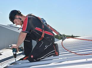 Arbeiter mit persönlicher Schutzausrüstung gegen Absturz (PSAgA) auf einem Dach
