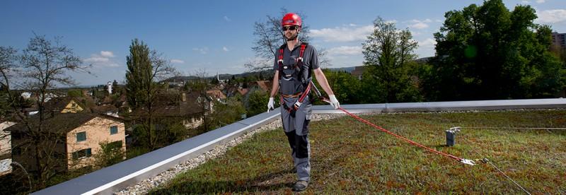 Arbeiter auf einem Flachdach ist mit seinem Verbindungsmittel am Seilsicherungssystem gesichert