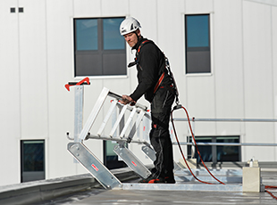 Montage eines mobiles Schutzgeländers auf einem Flachdach