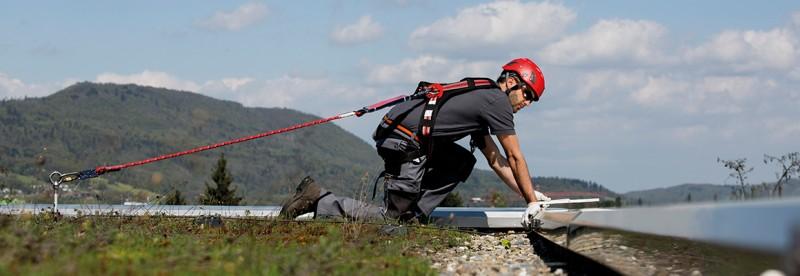 Arbeiter in der Nähe der Absturzkante mit PSAgA gesichert auf einem Flachdach