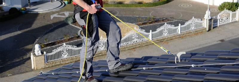 Arbeiter auf Steildach am Sicherheitsdachhaken gegen Absturz gesichert