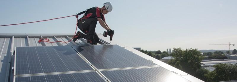 Gegen Absturz gesicherter Solar-Installateur auf einem Steildach