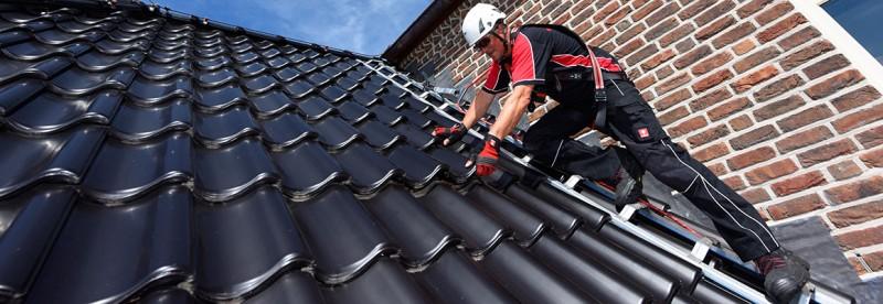 Arbeiter auf Steildach, der an einem Sicherheitsdachhaken gegen Absturz gesichert ist